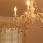 Hang strings of ornaments on your chandelier.